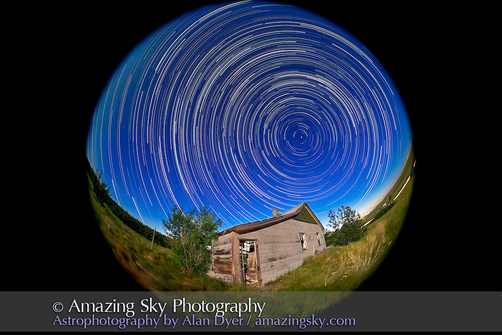 A circumpolar star trail shot, with an old farm shed as the landscape focus. Taken July 14, 2011 at an old farmstead near home in southern Alberta. This is a stack of 660 17-second exposures, 1s apart, taken with the Canon 5D MkII at ISO 800 and 8mm lens  at f/4.5, taken over 3.5 hours from 11:15 pm to 2:42 am. Light from Full Moon (off frame at top) illuminated the landscape and made the sky blue. Images stacked the Chris Schur's Photoshop Action.