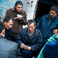 CHONGQING, CHINA - DEC 19, 2010: Chinese workers playing cards during a brake at the wholesale market in Chongqing.