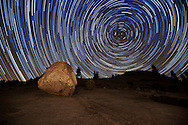 Star trails above large boulders and trees at Olmstead Point, Yosemite National Park