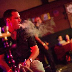 072910       Brian Leddy.Jace Frye smokes a hookah while enjoying Thursday night's music at the Juggernaut.