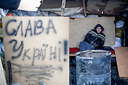 """Young protestor Roman at the barricades blocking a building supplies store named """"Epicenter"""" in the city of Lviv, Ukraine. The inscription reads """"Glory for the Ukraine"""" (Slavo Ukraina)."""