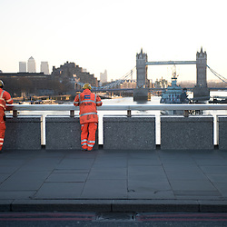 London, UK - 25 December 2014: two workers watch the sunrise behind Tower Bridge in London on Christmas morning.