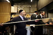 The process of baking unleavened matza bread for Passover finishes with the uncooked dough being put in a brick oven on a long wooden stick. The baking process from start to finish has to be completed within 18 minutes for it to be Kosher. They are baking matza bread for the festival of Passover out the back of Bethune Road synagogue.