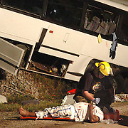 "The lives of 66 members of an Alabama family were forever changed when the the driver of a tour bus fell asleep and crashed into a bridge on Interstate 65. One family member was killed and more than 50 injured. A Warren County, Ky., volunteer firefighter  comforts a vicitim of an early morning bus crash June 25, 2007, on Interstate 65 four miles north of Smiths Grove, Ky. aekdb ""Bus Wreck"""