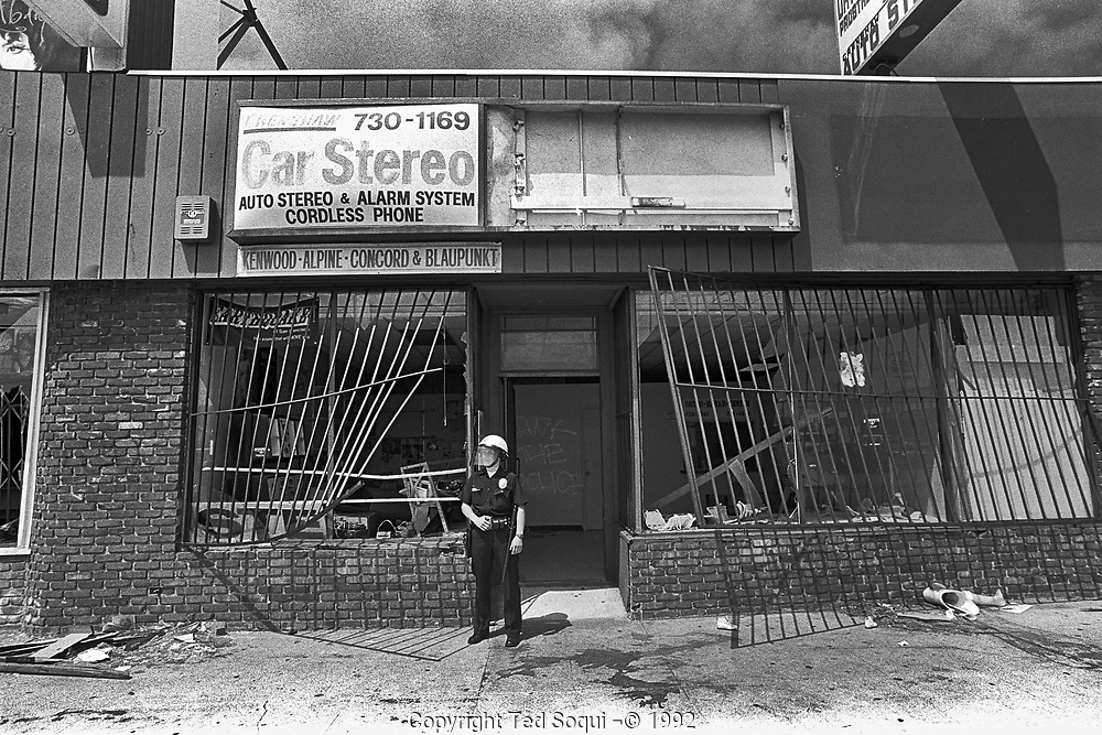 A LAPD police officer stands in front of a looted car stereo business on Crenshaw blvd. in South Central Los Angeles.