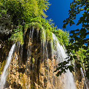 Mali Prstavac waterfall plunges 18 meters at the Upper Lakes (Gornja Jezera). Plitvice Lakes National Park (Nacionalni park Plitvicka jezera, in Croatia, Europe) was founded in 1949 and is honored by UNESCO as World Heritage Site. Waters flowing over limestone, dolomite, and chalk in this karstic landscape have, over thousands of years, deposited travertine barriers, creating natural dams, beautiful lakes and waterfalls. Warming conditions after the last Ice Age (less than 12,000 years ago) allowed the natural dams to form from tufa (calcium carbonate) and chalk depositing in layers, bound by plants. Plitvicka Jezera is a municipality of Lika-Senj County, in the Republic of Croatia.