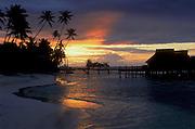 Sunset at Bora Bora Lagoon Resort, Tahiti, with beach, palm trees and overwater bungalows on lagoon..