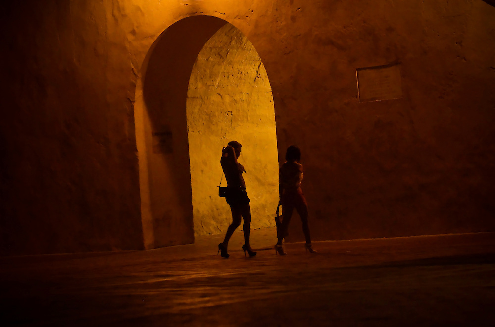 Women walk in a plaza by the clock tower in the historic center of Cartagena, Colombia. This coastal city boasts many bars and discotecs where foreign tourists can drink, dance, and pick up prostitutes. Prostitutes can be found openly soliciting clients all night in the plaza surrounding the clock tower, which is a zone where it is legal. A sex scandal erupted recently when secret service agents were found bringing prostitutes to their hotel rooms while in Cartagena preparing for President Barack Obama's arrival to the Summit of the Americas.