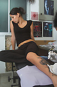 A young woman being tattooed on her leg in a tattoo studio
