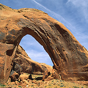 A tiny hiker (silhouetted in black) crosses beneath massive Broken Bow Arch, in Glen Canyon National Recreation Area, Utah, USA.