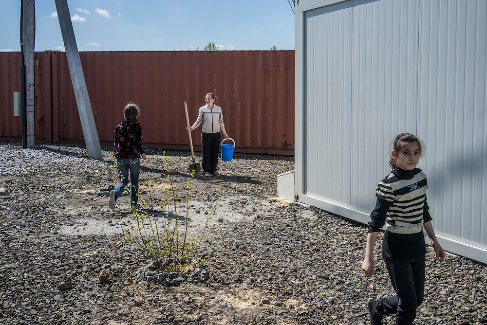 Svetlana Kravchenko, 42 (center), with her daughter Margo, 11 (right), and another young resident of a cluster of prefabricated container houses known as Transit City plant bushes on Monday, April 27, 2015 in Kharkiv, Ukraine. Kravchenko came from the village of Alchevsk, in the Lugansk region, forced to flee fighting in eastern Ukraine between Ukrainian forces and pro-Russian rebels. CREDIT: Brendan Hoffman/Prime for the Wall Street Journal UKRMIGRATION