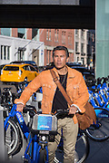 Asian American man walking with a citibike in New York City