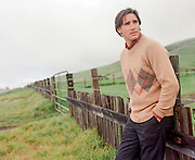 handsome man leaning against a wooden fence in Northern California