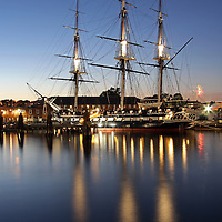 Boston night photography image of the historic USS Constitution battleship, also known as Old Ironsides, mooring in the Charlestown Navy Yard in historic Boston, Massachusetts. Boston Fireworks going off to the right of Old Ironsides. <br />