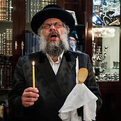 London, UK - 13 April 2014: Rabbi Osher Schapiro of the Jewish Community of Stamford Hill recites blessings before searching for chametz (leavened bread products) in his house on the night before Passover.