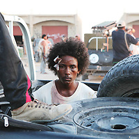 A suspected pro Gaddafi fighter from Chad who rebel forces say they captured with an RPG sits in the back of a pickup truck on the outskirts of Sirte, Libya. September 2011.