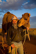 Camel Trek just outside William Creek in North Eastern South Australia. Philip Gee with camel Sir Wobble on the sand dunes outside William Creek.Considered to be one of Australia's leading camel men Philip Gee has been a senior guide with Explore the Outback camel safaris since 1987 and he has trained hundreds of wild camels. Philip who is a specialist Historian has led countless expeditions into this wilderness over the past 20 years and knows the Lake Eyre desert country very well. Explore the Outback camel safaris are based in the central Australian deserts near William Creek along the Oodnadatta Track (Lake Eyre, South Australia), and operate from April through to October every year...Explore the Outback camel safaris are based in the central Australian deserts near William Creek along the Oodnadatta Track (Lake Eyre, South Australia), and operate from April through to October every year.