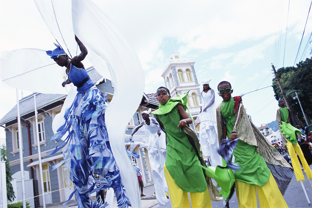 """Trinidad and Tobago """"MOKO JUMBIES: The Dancing Spirits of Trinidad"""".(The energy is palpable as Jumbie Bat John Sterling and Bamboo Bug Men Moko Jumbies dance down Frederick Street in Port of Spain.).A photo essay about a stilt walking school in Cocorite, Trinidad..Dragon Glen de Souza founded the Keylemanjahro School of Art & Culture in 1986. The main purpose of the school is to keep children off the streets and away from drugs..He first taught dances like the Calypso, African dance and the jig with his former partner Cathy Ann Samuel.  Searching for other activities to engage the children in, he rediscovered the art of stilt-walking, a tradition known in West Africa as the Moko Jumbies , protectors of the villages and participants in religious ceremonies. The art was brought to Trinidad by the slave trade and soon forgotten..Today Dragon's school has over 100 members from age 4 and up..His 2 year old son Mutawakkil is probably the youngest Moko Jumbie ever. The stilts are made by Dragon and his students and can be as high as 12-15 feet. The children show their artistic talents mostly at the annual Carnival, which today is unthinkable without the presence of the Moko Jumbies. A band can have up to 80 children on stilts and they have won many of the prestigious prizes and trophies that are awarded by the National Carnival Commission. Designers like  Peter Minshall , Brian Mac Farlane and Laura Anderson Barbata create dazzling costumes for the school which are admired by thousands of  spectators. Besides stilt-walking the children learn the limbo dance, drumming, fire blowing and how to ride  unicycles..The school is situated in Cocorite, a suburb of Port of Spain, the capital of Trinidad and Tobago..all images © Stefan Falke"""