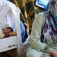 Syrian refugee Peroz Ismail, 27-years-old, next to her daughter Hawler on their blanket in Quashtapa Park in Quashtapa, Iraq outside of Erbil in Iraqi Kurdistan, Saturday, August 31, 2013. Peroz Ismail left her home in Syria last week with her 3 day old daughter Hawler and her other 3 other children. For the past week the family has been living on a blanket with hundreds of other Syrian refugees in a small park on the outskirts of Erbil. August 2013.