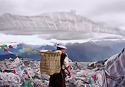 Summit of Mt. Kongpo Bonri. Kongpo region, Tibet. Religious pilgrim adds prayer flags.