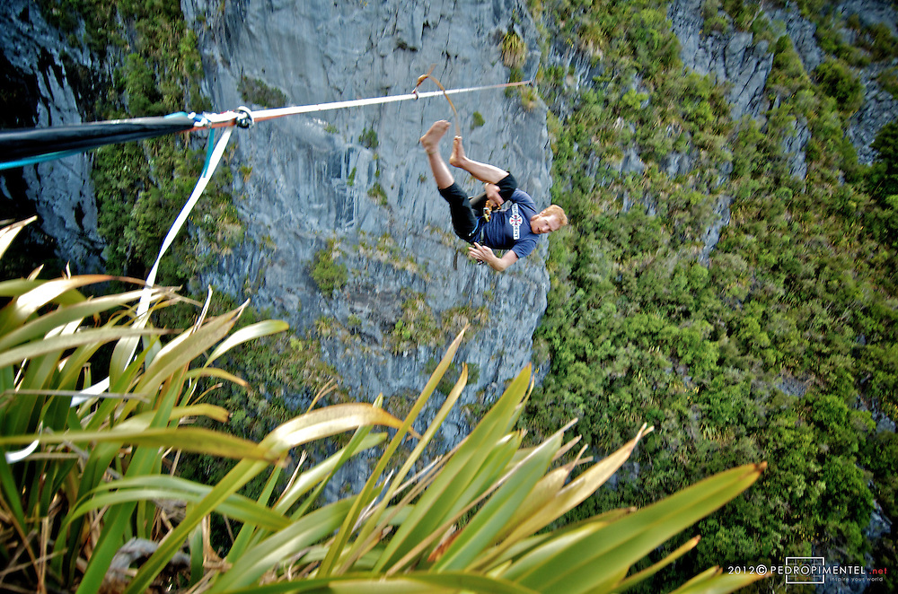Shanes Yate on an epic leash journey looking down into the 250m high exposure.  New Zealand.