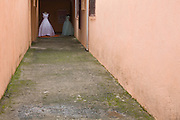 Two wedding dresses outside  a shop down a passage in Cubatão