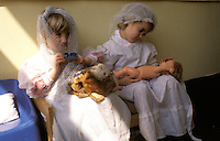 Boy and girl playing wih dolls.