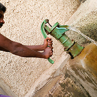 Man pumping water in blocks of flats at Santhome. Santhome Beach and adjoining Marina Beach in Chennai, India were hit hard by the 2004 Tsunami. Fishermen and their families were the main victims living in their lightweight huts on the long and flat beaches of the area. All structures within 300 metres of the sea have now been banned and any left standing after the Tsunami were demolished. The fishermen and their families have now been relocated to government blocks of flats which has become a Santhome slum for fishermen and their families.