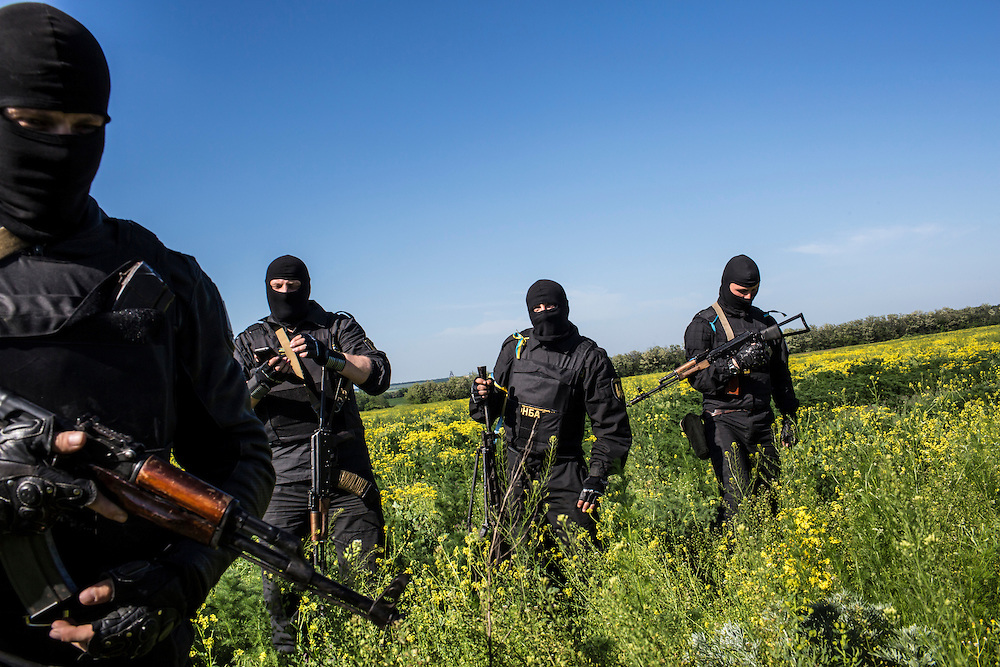 DOBROPILLYA, UKRAINE - MAY 21:  Members of the Donbass Battalion, a pro-Ukraine militia, stand in a field near a Ukrainian military checkpoint on May 21, 2014 in Dobropillya, Ukraine. Days before presidential elections are scheduled, questions remain whether the eastern regions of Donetsk and Luhansk are stable enough to administer the vote. (Photo by Brendan Hoffman/Getty Images) *** Local Caption ***