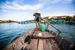 A Vietnamese woman rows a barge along Thu Bon River in Hoi An, Vietnam, Southeast Asia