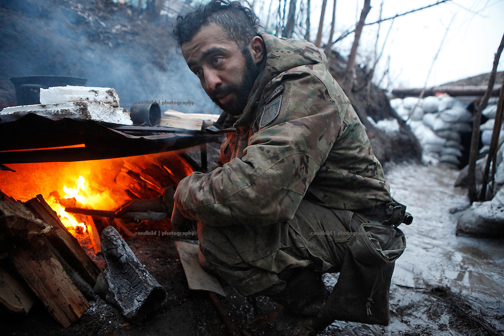 Ben sits in front of a small camp fire in his trench position at Donetsk frontline.<br /> <br /> +++   +++ The Boom Stick Brotherhood +++   +++  <br /> <br /> Driven by a certain fascination on military and a simple shaped nationalistic ideology young men travel the world to fight at frontlines of recent conflicts. Five volunteering warriors from europe and the US were walking into battle in Ukraine last year. Ben, Alex, Craig, Charlie and Cowboy made it to the frontline joining the right-wing militia Right Sector (Prawji Sektor) to defend Ukraine by fighting seperatists and russian irregular forces aiming to split off the eastern Donbass region from the country.<br /> <br /> As ukrainian forces are short of servicemen Right Sector is welcomed to support the defense efforts at hotspots. Receiving no payments but shelter, food and ammonition the foreigners selfmade battlegroup Task Force Pluto found itself in a so called Anti-Terror-Operation close to the Donetsk Airport. Though Minsk II Agreement for Ceasefire is in effect several daily fire exchanges taking place between both conflict parties at the line of contact. However the war is now fought in a World War I alike stalemate in muddy trenches which were digged during the World War II.<br /> <br /> As a loose union of individuals the Boom Stick Brotherhood is no certain ukrainian phenomenon and not tied to the recent war only. If things would become boring, crazy or if the army leadership would deter foreigners from fighting Ben and his comrades would move on looking for another destination around the globe to be involved in battle. That&acute;s what they are aiming for. They are living a dream of smoking guns, camaraderie and a simple outdoor life. A lifestyle devoted to look every day into the ugly face of death.<br /> <br /> The Boom Stick Brotherhood is a multi-national, multi-religious and multi-ethnic group of men in its twenties:<br /> Ben, an austrian infantryman travelling to hot zones since years. Bored