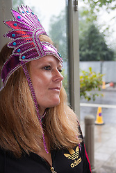 London, August 25th 2014. A woman waits for a break in the weather as final touch ups to costumes are made as Notting Hill Carnival goers prepare to party despite the pouring rain.