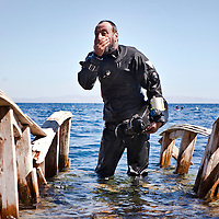 "Tarek Omar, a tech and recovery diver,  leaves the water after a dive in the Blue Hole outside of Dahab, Egypt. The Blue Hole is notorious for the number of diving fatalities which have occurred there, earning it the sobriquet ""World's Most Dangerous Dive Site"" and the nickname ""Diver's Cemetery"". The site is signposted by a sign that says ""Blue hole: Easy entry"". Accidents are frequently caused when divers attempt to find the tunnel through the reef (known as ""The Arch"") connecting the Blue Hole and open water at about 52 m depth. According to dive experts roughly 10 people die each year. April 2012."