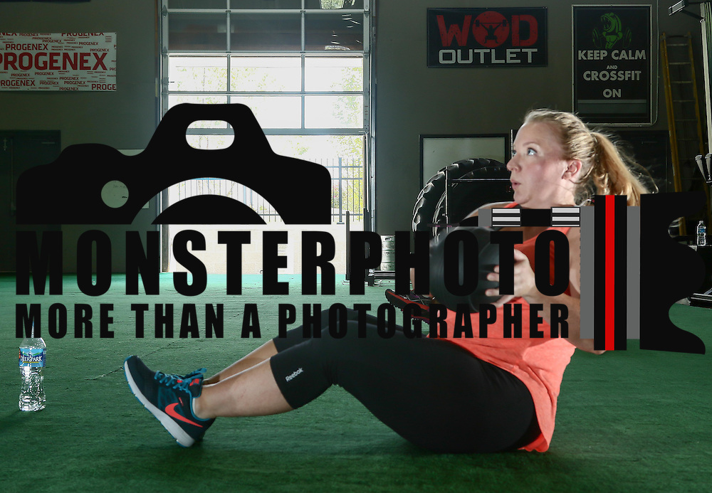 Katie Hemming who is 6 and a half months pregnant uses a medicine ball during a CrossFit class Thursday, August 18, 2016, at CrossFit Riverfront in Wilmington.