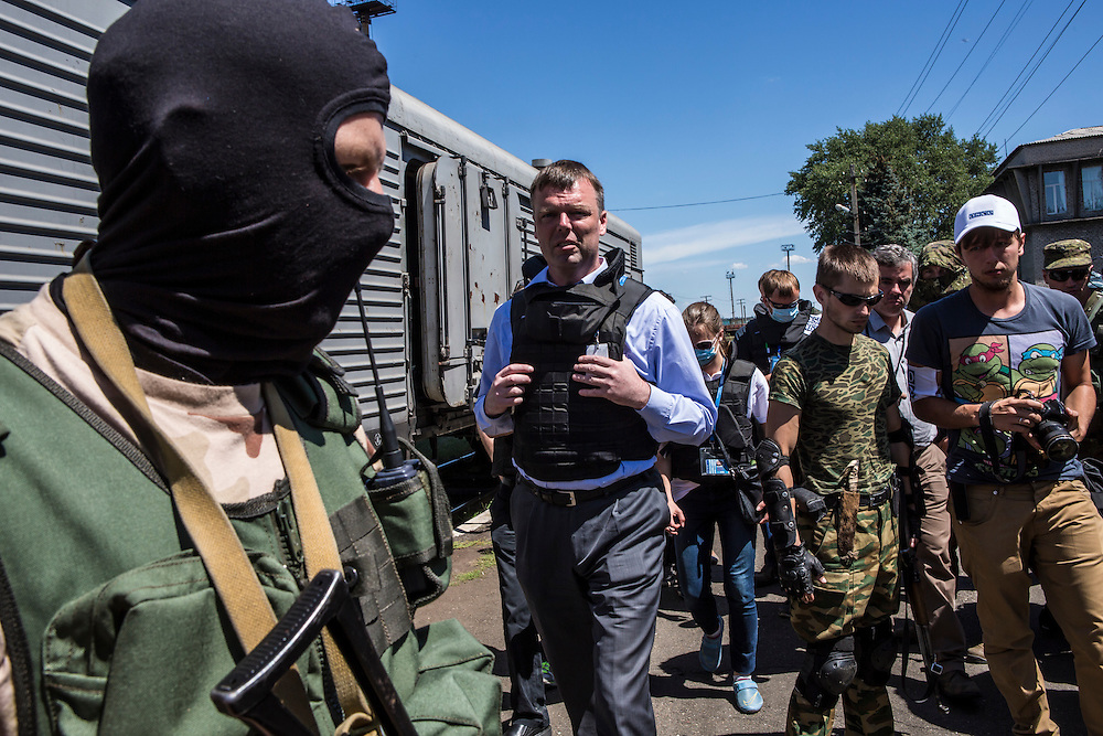 TOREZ, UKRAINE - JULY 21: Alexander Hug (C), Deputy Chief Monitor of the Organisation for Security and Cooperation in Europe (OSCE) Special Monitoring Mission to Ukraine, visits a train containing the bodies of victims of the Malaysia Airlines flight MH17 crash on July 21, 2014 in Torez, Ukraine. Together with Dutch inspectors, the storage conditions were declared acceptable, though it is still unclear where or when the train will be moved. Malaysia Airlines flight MH17 was travelling from Amsterdam to Kuala Lumpur when it crashed killing all 298 on board including 80 children. The aircraft was allegedly shot down by a missile and investigations continue over the perpetrators of the attack. (Photo by Brendan Hoffman/Getty Images) *** Local Caption ***  Alexander Hug
