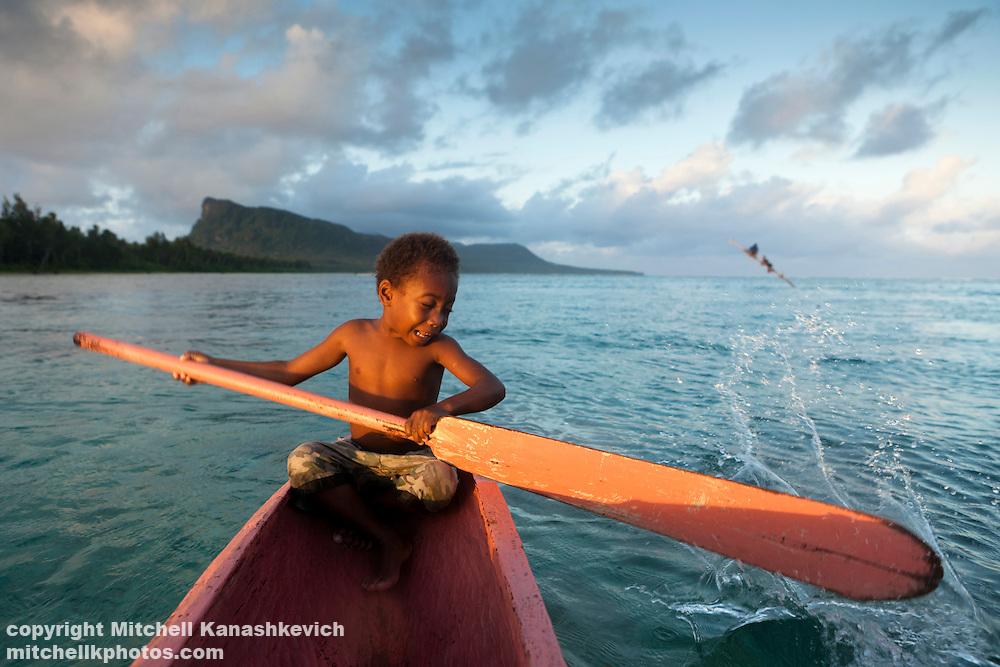 Young Ni Vanuatu boy trying to steer a canoe in the lagoon between the islands of Mota and Rah Lava. Rah Lava Island, Torba Province, Vanuatu