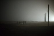 March 27, 2017 – Emerson, Manitoba : A group of migrants from Djibouti and Somalia stand in a field in North Dakota prior to entering Canada illegally at Emerson, Manitoba at 4 am.