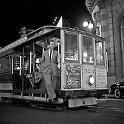 Herb Caen  riding on a San Francisco Cable Car