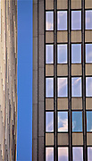 Photograph a section of the side of one building with a frontal view of the skyscraper next door.