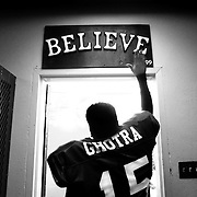 "Heeding a pre-game ritual that was initiated in 1999, Atwater High senior Gurwinder Ghotra touches the ""Believe"" sign posted above the Falcons' locker room exit before heading out to the playing field for a Friday-night contest."