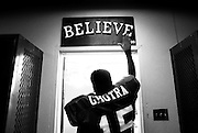 """Heeding a pre-game ritual, senior Gurwinder Ghotra touches the """"Believe"""" sign posted above the Atwater High Falcons' locker room door before Friday night football in Atwater, California."""