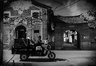 "Bai woman on motor-trishaw passes a typicle Bai version of trompe l'oeil and Xizhou's eastern ""Dong An Men"" gate.  Xizhou, near Dali, Yunnan, China."
