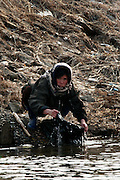 A North Korean woman washes clothes in the Yalu river in Sinuiju, North Korea, on Wednesday, Feb.  9, 2007. As The Six Party talks resume in Beijing the US envoy is ompimistic on North Korean nuclear talks.