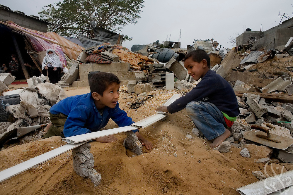 Palestinian children from the al-Bahabsa family use rubble from their destroyed home to build sand castles and bridges as they play January 23, 2009 in the Juhor al-Dik neighborhood southeast of Gaza City. The 21 member family is now homeless after their family compound was destroyed by Israeli tanks and bulldozers during the recent 22 day Israeli military operation in the Gaza strip. According to the UNited Nations, some 840, 000 Gaza children are under extreme stress and have been traumatized by the violent events of the recent weeks.