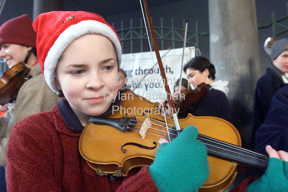 20/12/98 EXAMINER.AOIFE RYAN AGED 13 OF THE KILKENNY YOUTH ORCHESTRA PICTURED PLAYING IN THE THOLSEL ON THE STREETS OF KILKENNY YESTERDAY.THE ORCHESTRA WERE PLAYING TO RAISE FUNDS FOR THE SAMARATINS.PICTURE DYLAN VAUGHAN.
