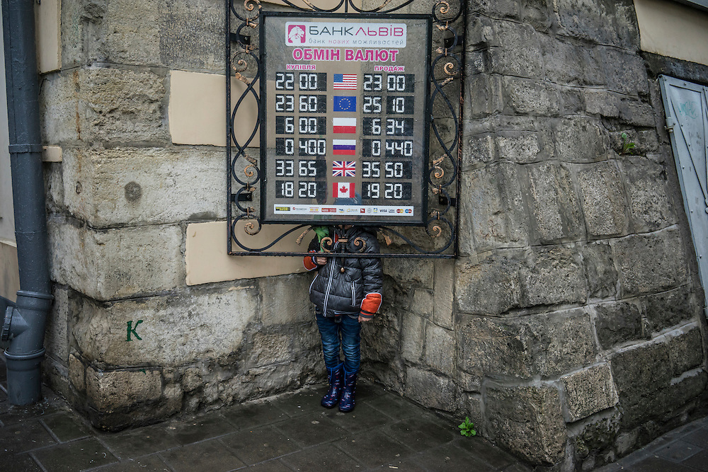 Yaroslav Kirichuk, 6, hides behind a sign on his way home from school on Tuesday, April 28, 2015 in Lviv, Ukraine. After his father joined forces with pro-Russian rebels in eastern Ukraine, his mother Olga left him and other members of her family with anti-Ukrainian views and took her son to Lviv, where they live with a friend. CREDIT: Brendan Hoffman/Prime for the Wall Street Journal UKRMIGRATION