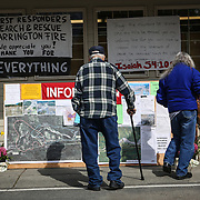 A resident reads an information board at the Darrington IGA grocery store on Monday, March 31, 2014. Work continues in the debris field of the nearby Oso mudslide. (Joshua Trujillo, seattlepi.com)
