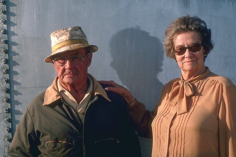 Duncan, Oklahoma setting sun on an oiltank, converted to a hay and seed barn. Portrait of Preston Cash in his element, with his wife, Leona, by his side.