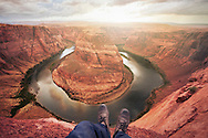 Point of view with two feet overlooking the Colorado River at Horseshoe Bend, Page, Arizona.