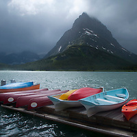 Boats on Many Glacier Lodge Dock at Swiftcurrent Lake under Grinnell Peak and Storm Clouds, Glacier National Park, Montana, US